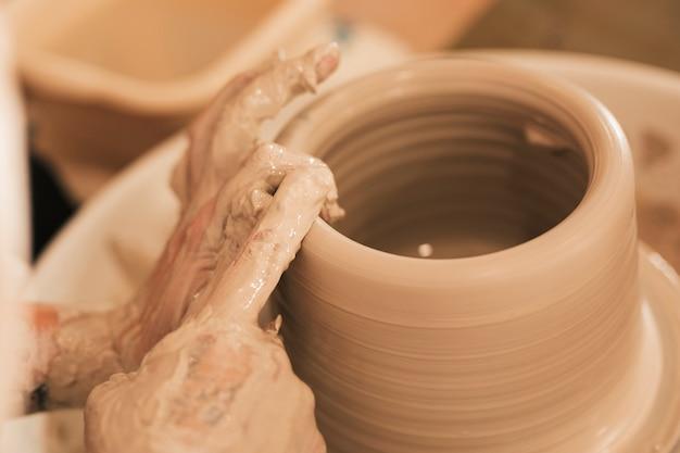 Pottenbakker die ceramische pot op het aardewerkwiel maakt