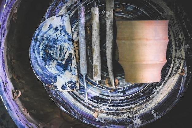 Pottenbakkersgereedschap close-up op het pottenbakkerswiel. atelier aardewerk. meester kruik. culturele tradities. handgemaakt. ambacht. gedraaid pottenbakkerswiel.
