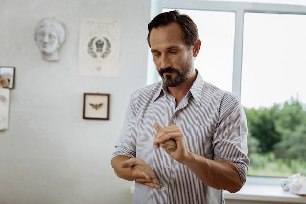 Pottenmaker. donkerharige pottenbakker met baard die zich bedachtzaam voelt terwijl hij hard aan het werk is in zijn werkplaats