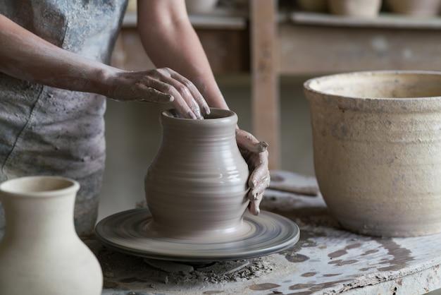 Potter beeldhouwt een vaas op een pottenbakkerswiel