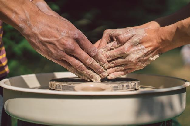 Potter die een klei-object maakt op een aardewerkwiel in de buitenlucht ambachtsman die klei vormt met de handen op potten...