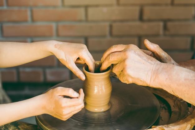 Potter leert om een kleipot te beeldhouwen