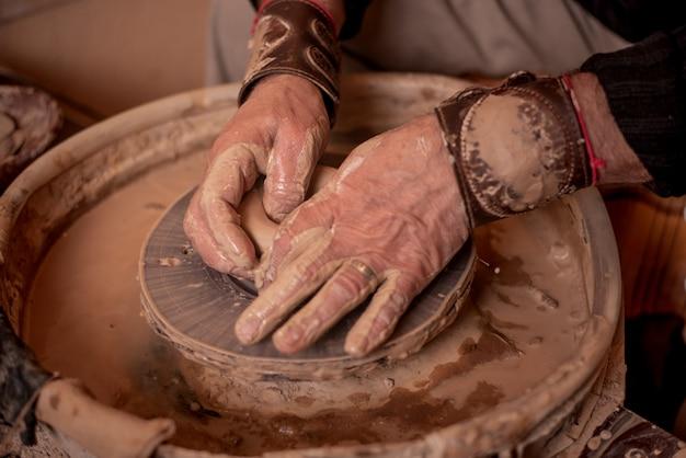 Potter's handen werken met klei, waardoor het een product is