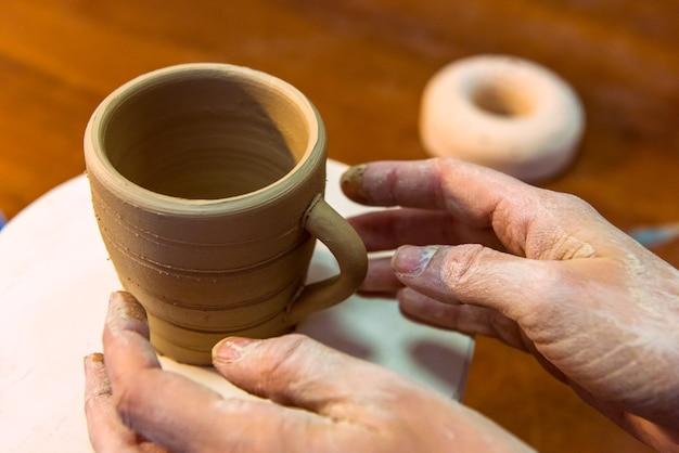 Pottering - het maken van een kleikop in proces. geschoten met een kleine grip