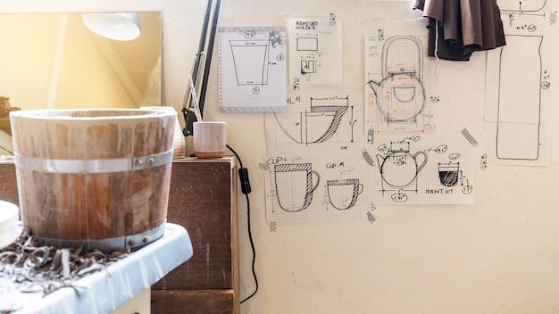 Pottery wheel machine voor het maken van handgemaakt keramiek en houten vat met vele soorten keramiek schetspapier op de muur. creatieve werkplaatsstudio.