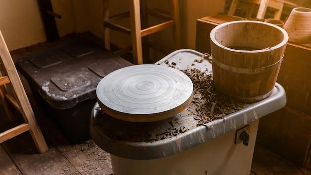 Pottery wheel machine voor het maken van handgemaakte keramiek zoals kommen, borden en kopjes op de voorgrond met houten vat. creatieve workshop.