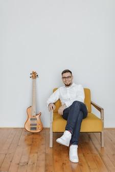 Pottret van mooie jonge man gitaarspelen zittend op de bank in huis.