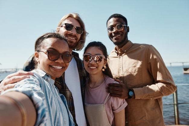 Pov bij diverse groep jongeren die in de zomer buiten selfies nemen, allemaal met een zonnebril