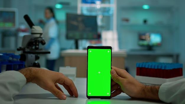 Pov-opname van een man-wetenschapper die aan een bureau zit en aan een mobiele telefoon werkt met een mock-up groen scherm, geïsoleerd display. in achtergrondlaboratoriumonderzoeker die vaccinontwikkeling analyseert en monsters onderzoekt