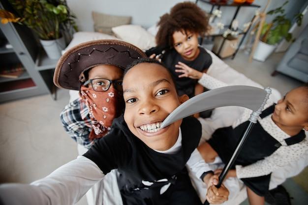 Pov-opname van lachende afro-amerikaanse kinderen die halloween-kostuums dragen terwijl ze thuis een selfie maken.