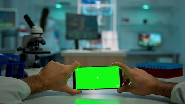 Pov-opname van scheikundige met behulp van horizontale smartphone met chromakey op geïsoleerd display in biologisch laboratorium. dokter draagt witte jas in kliniek die werkt met mobiel met groen scherm in medisch laboratorium