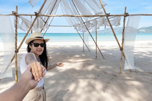 Pov point of view volg mij vrouw met zonnebril leidt vriendje met de hand naar de zee