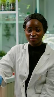 Pov van afrikaanse vrouw zittend aan bureautafel in farmaceutisch laboratorium tijdens online videocall-vergadering. specialistenteam dat genetische mutatie onderzoekt en dna-ggo-biologietest ontwikkelt