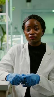 Pov van botanicus-onderzoekervrouw die botanie-experiment uitlegt tijdens online videogesprekvergadering terwijl ze in een farmaceutisch laboratorium zit. specialistenteam dat genetische mutatie onderzoekt en dna-test ontwikkelt