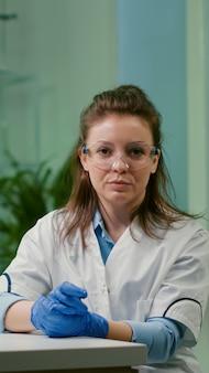 Pov van botanicusvrouw in witte jas luisterend chemici-team tijdens online videogesprek