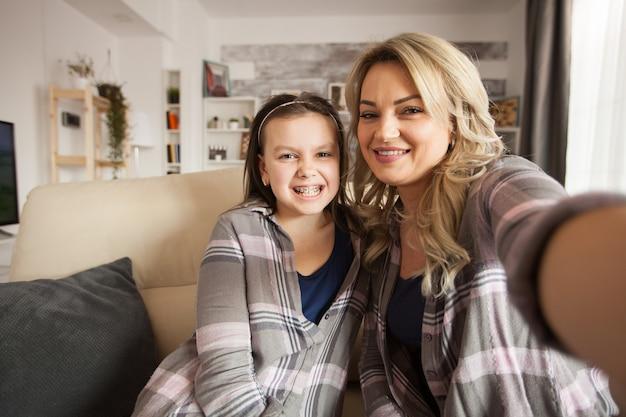 Pov van een klein meisje met een grote glimlach die haar beugel laat zien terwijl haar moeder op de bank zit.