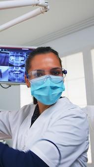 Pov van een patiënt in een tandheelkundige kliniek die op een operatiestoel zit en de aangetaste massa controleert. tandheelkundeteam dat in een orthodontisch kantoor werkt, de lamp aansteekt en persoon onderzoekt, close-up gezicht met medisch masker.
