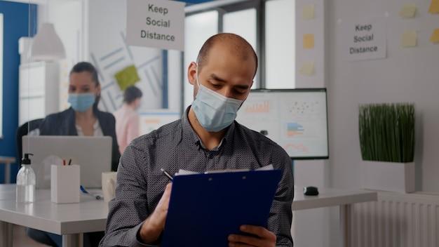 Pov van freelancer met beschermend gezichtsmasker op zoom online videogesprek conferentievergadering. zakenman die in een nieuw normaal kantoor werkt tijdens de wereldwijde pandemie van het coronavirus, houd borden voor sociale afstand op de