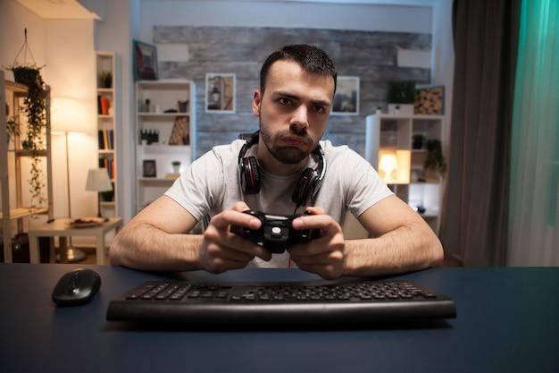Pov van geconcentreerde jongeman die online schietspel speelt op stream met draadloze controller.