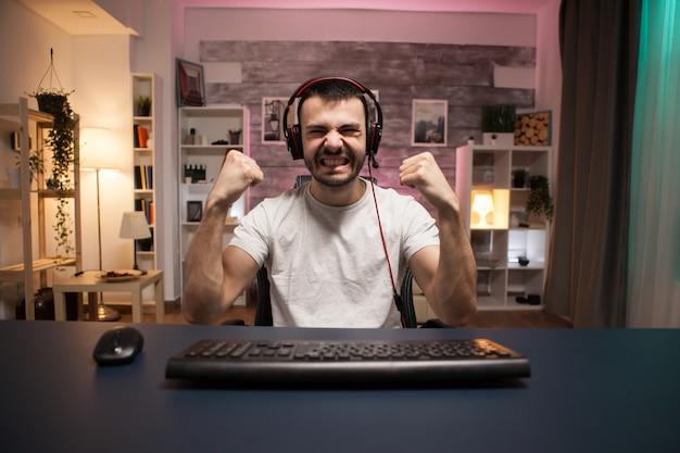 Pov van jonge man enthousiast over zijn winnen tijdens het spelen van schietspellen op stream.