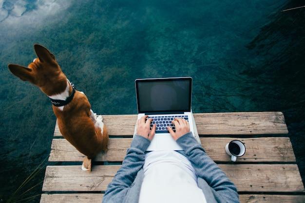 Pov van man drinkt koffie en werkt op laptop aan het meer