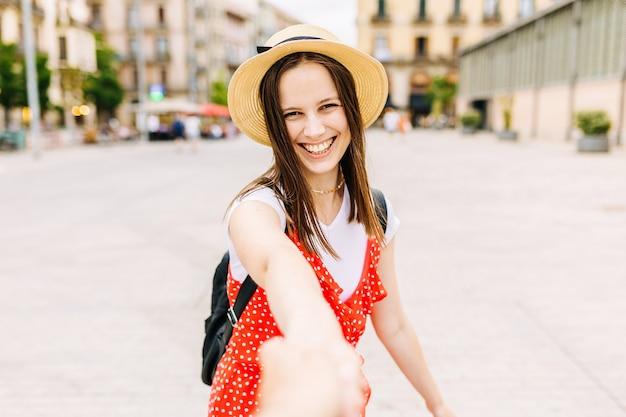 Pov van man met lachende vrouw hand in de stad - jong toeristisch koppel hand in hand tijdens het reizen - mooie koppels en zomervakantie concept - focus op het gezicht van de vrouw