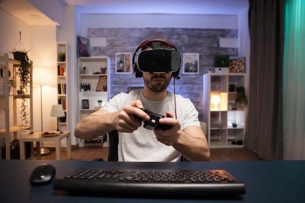Pov van online shooter-gamer die een virtual reality-bril draagt tijdens het gebruik van een draadloze controller.