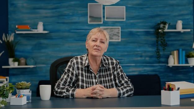 Pov van oudere bejaarde vrouw die zwaait tijdens een videoconferentie met zakenpartners die vanuit huis werken