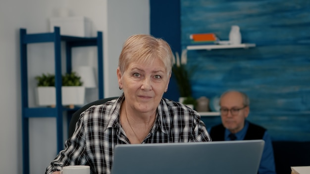 Pov van oudere bejaarde vrouw die zwaait tijdens een videoconferentie met zakenpartners die vanuit huis werken ...