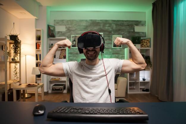 Pov van professionele gamer die zijn spieren buigt en zijn overwinning viert op online schietspel.