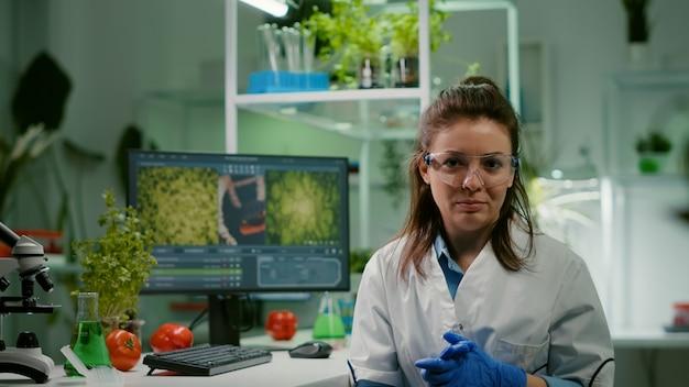 Pov van scheikundige vrouw in witte jas analyseren met biologen team tijdens online videocall