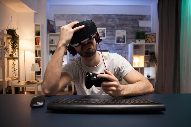 Pov van trieste jongeman na game over bij online games op stream met behulp van controller.