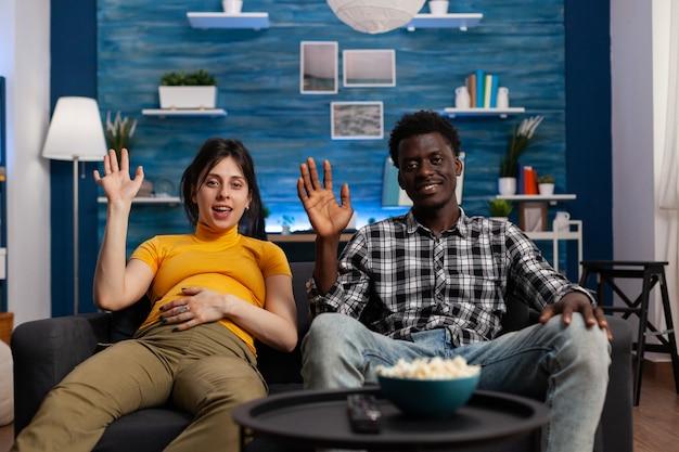 Pov van zwanger interraciaal koppel dat video-oproepcommunicatie gebruikt terwijl ze op de bank zitten. liefhebbers van gemengd ras met technologie zwaaien naar online conferentiecamera op afstand die met familieleden praat