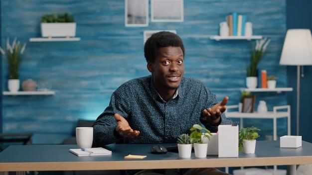 Pov zwarte man op online videoconferentiegesprek met teamgenoten, praten met de camera, online virtuele communicatie hebben. internetonderwijs op afstand en conversatie via webcam