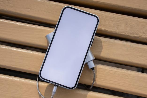 Power bank laadt een mockup smartphone met wit scherm op een houten bankje in het park.