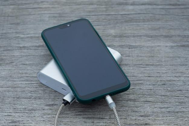 Power bank laadt een smartphone op een houten bankje in het park.