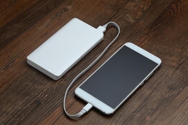 Powerbank en mobiele telefoon op houten tafel