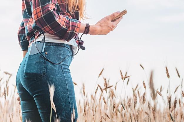 Powerbank in de achterzak van een meisje in een geel veld laadt de telefoon op.
