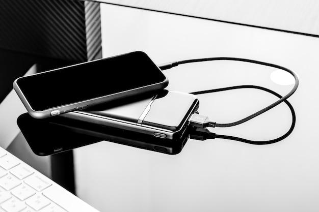 Powerbank laadt smartphone op zwarte oppervlakte wordt geïsoleerd die