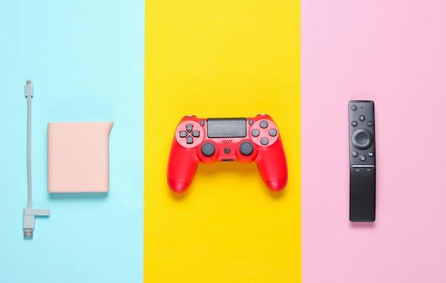 Powerbank, rode gamepad, tv-afstandsbediening op een achtergrond van gekleurd papier. bovenaanzicht.