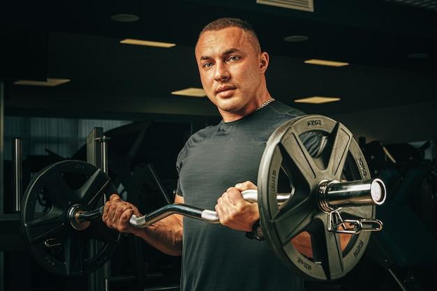 Powerlifter met sterke armen tillen halter in een sportschool