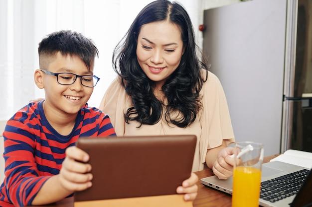 Ppetty lachende jonge vrouw kijken naar educatieve video op digitale tablet met haar preteen zoon tijdens het verblijf thuis