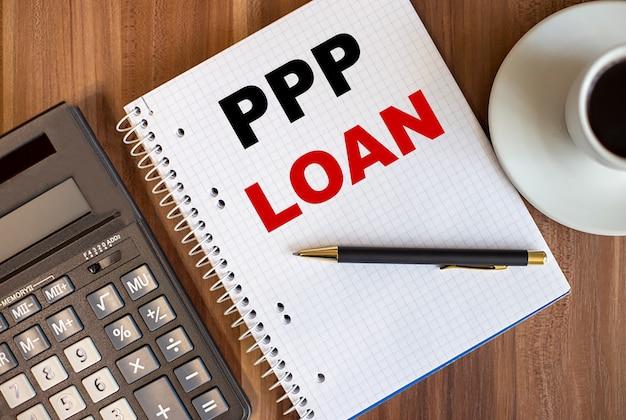 Ppp-lening geschreven in een wit notitieblok in de buurt van een rekenmachine en een kopje koffie op een donkere houten achtergrond