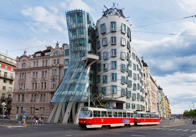 Praag - 20 augustus: dansend huis met passerende tram op 20 augustus 2014 in praag. the dancing house is ontworpen in 1992 door vlado milunic en frank gehry en voltooid in 1996