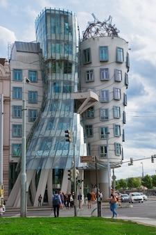 Praag - 20 augustus: straat met dansend huis op 20 augustus 2014 in praag. the dancing house is ontworpen in 1992 door vlado milunic en frank gehry en voltooid in 1996