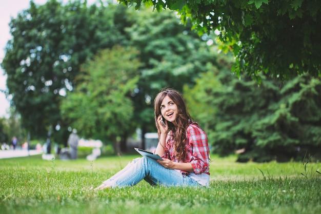 Praat aan de telefoon in het park. internet / communicatie / communie.