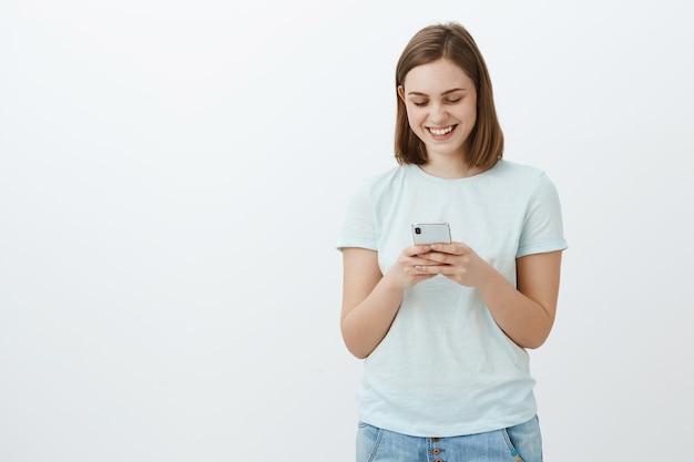 Praat later. ik kreeg bericht van vriend. blij aantrekkelijk jong onbezorgd meisje met kort bruin kapsel bedrijf mobiele telefoon tekst typen in smartphone glimlachen terwijl gelukkig starend naar het scherm van het apparaat