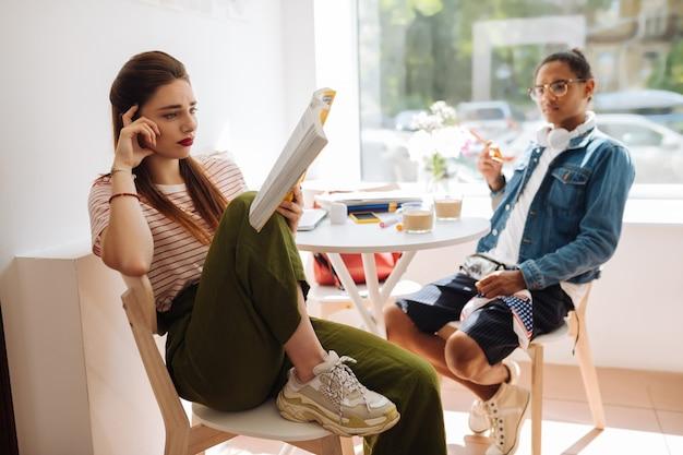Praat met mij. emotioneel langharig meisje dat haar voorhoofd rimpelt tijdens het lezen van een boek