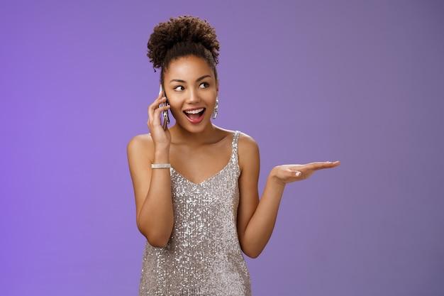 Praatzuchtige, gezellige aantrekkelijke elegante afro-amerikaanse vrouw in glinsterende zilveren jurk gebaren beschrijven partij pratende smartphone opzoeken geamuseerd hebben leuk vriendelijk gesprek, blauwe achtergrond.