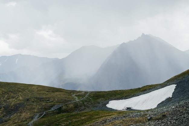 Prachtig alpien landschap met gigantische berg met puntige top in zonlicht door wolken.